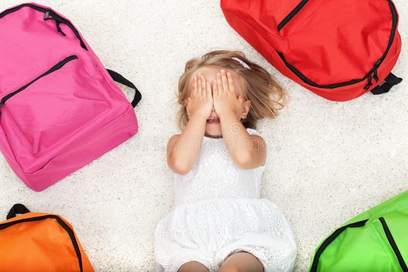 Kleines Mädchen, das unter bunten Schultaschen liegt lizenzfreies stockbild