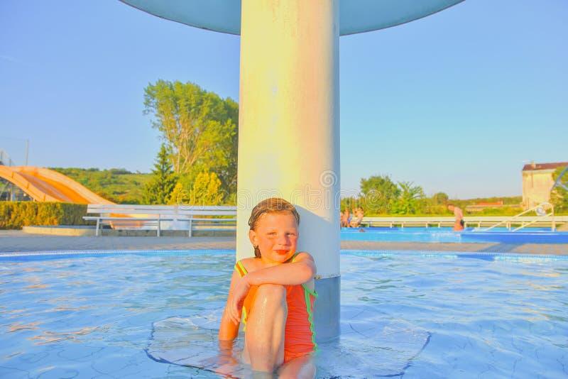 Kleines Mädchen, das unter einer Berieselungsanlage, Dusche im Swimmingpool sitzt Porträt des kleinen netten Mädchens im Swimming stockbilder