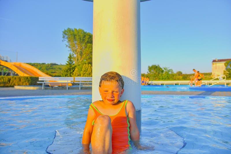 Kleines Mädchen, das unter einer Berieselungsanlage, Dusche im Swimmingpool sitzt Porträt des kleinen netten Mädchens im Swimming lizenzfreie stockfotografie