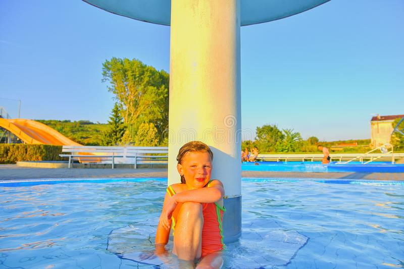 Kleines Mädchen, das unter einer Berieselungsanlage, Dusche im Swimmingpool sitzt Porträt des kleinen netten Mädchens im Swimming lizenzfreies stockfoto