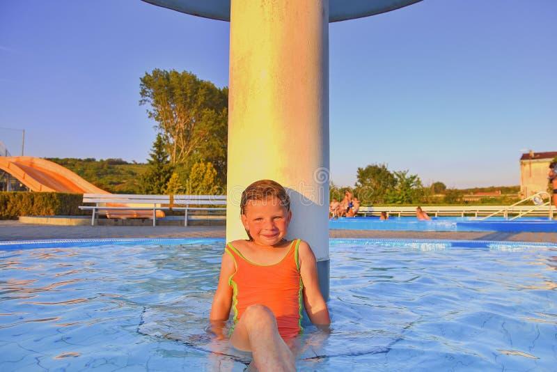 Kleines Mädchen, das unter einer Berieselungsanlage, Dusche im Swimmingpool sitzt Porträt des kleinen netten Mädchens im Swimming lizenzfreie stockbilder