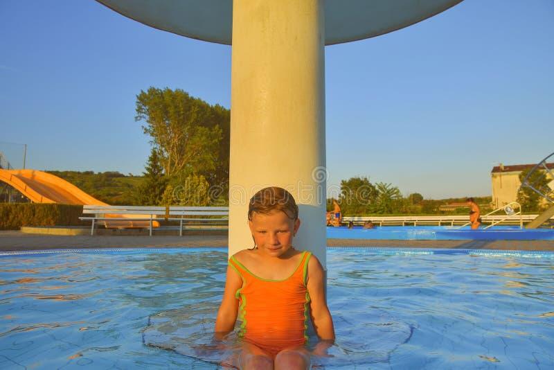 Kleines Mädchen, das unter einer Berieselungsanlage, Dusche im Swimmingpool sitzt Porträt des kleinen netten Mädchens im Swimming stockfotografie