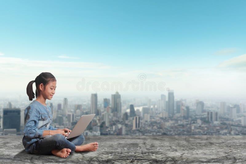 Kleines Mädchen, das unter Verwendung der Laptop-Computers auf modernen Stadtskylinen sitzt lizenzfreie stockbilder