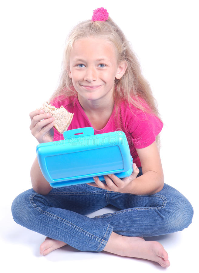 Kleines Mädchen, das vom Mittagessenkasten isst stockbilder