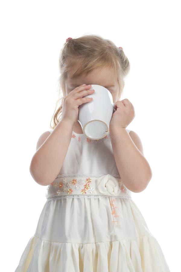 Kleines Mädchen, das vom weißen Cup trinkt stockfoto