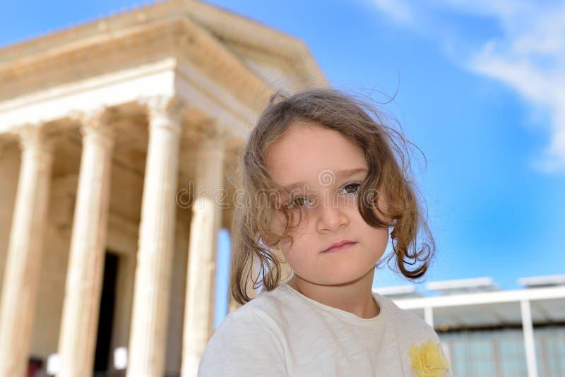 Kleines Mädchen, das vor einem römischen Tempel aufwirft stockfotografie