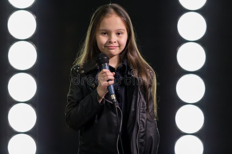 Kleines Mädchen, das vor Stadiumslichtern singt lizenzfreies stockfoto