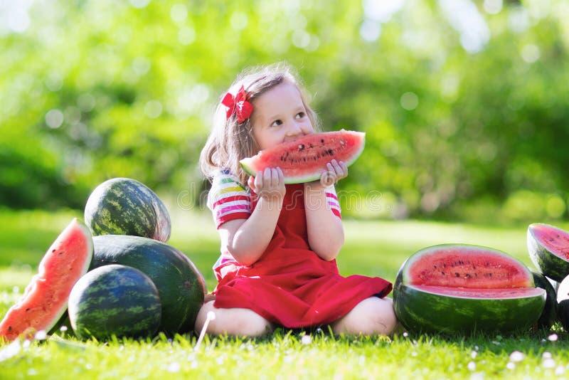 Kleines Mädchen, das Wassermelone im Garten isst stockfotografie