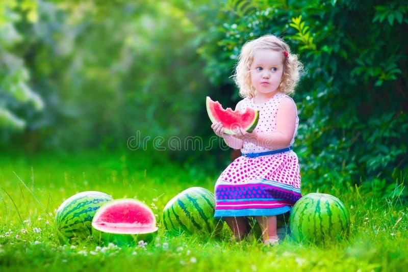 Kleines Mädchen, das Wassermelone isst stockfotos