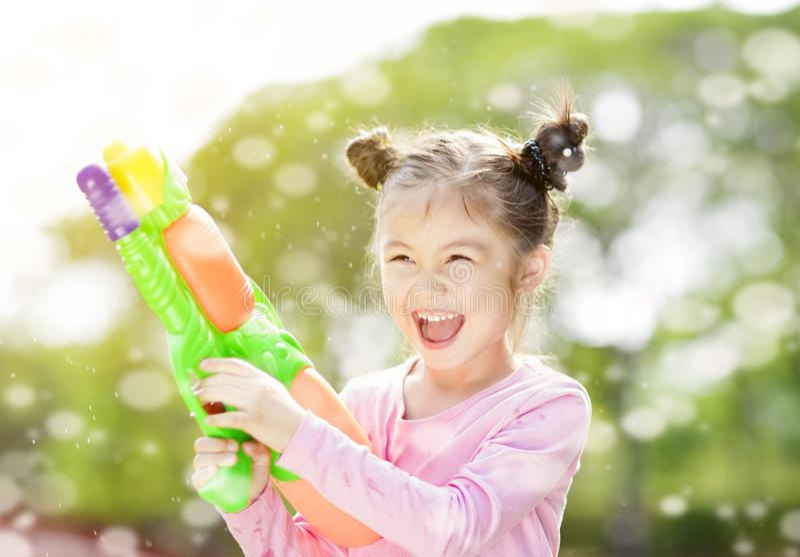 kleines Mädchen, das Wasserwerfer spielt stockfotos