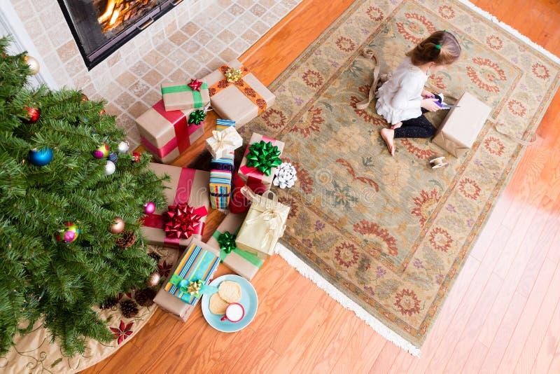 Kleines Mädchen, das Weihnachtsgeschenke in ihrem Wohnzimmer einwickelt stockbild
