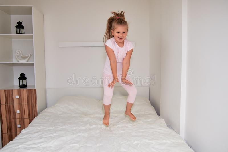 Kleines Mädchen, das zu Hause auf Bett springt stockfoto