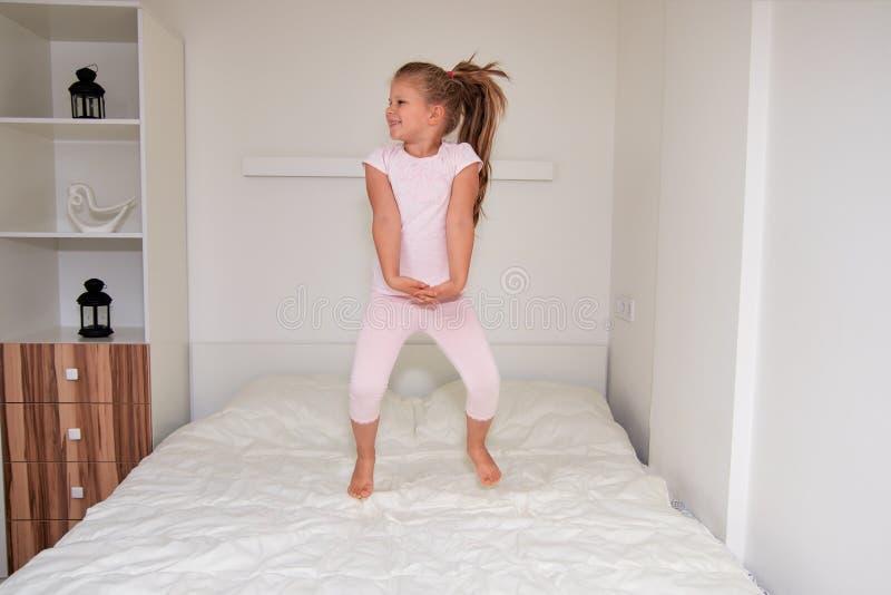 Kleines Mädchen, das zu Hause auf Bett springt lizenzfreie stockbilder