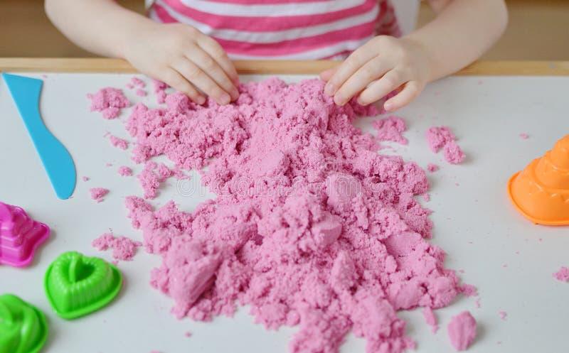 Kleines Mädchen, das zu Hause mit der rosa kinetischen Sand-Früherziehung sich vorbereitet für Schulentwicklungs-Kinderspiel spie lizenzfreies stockfoto