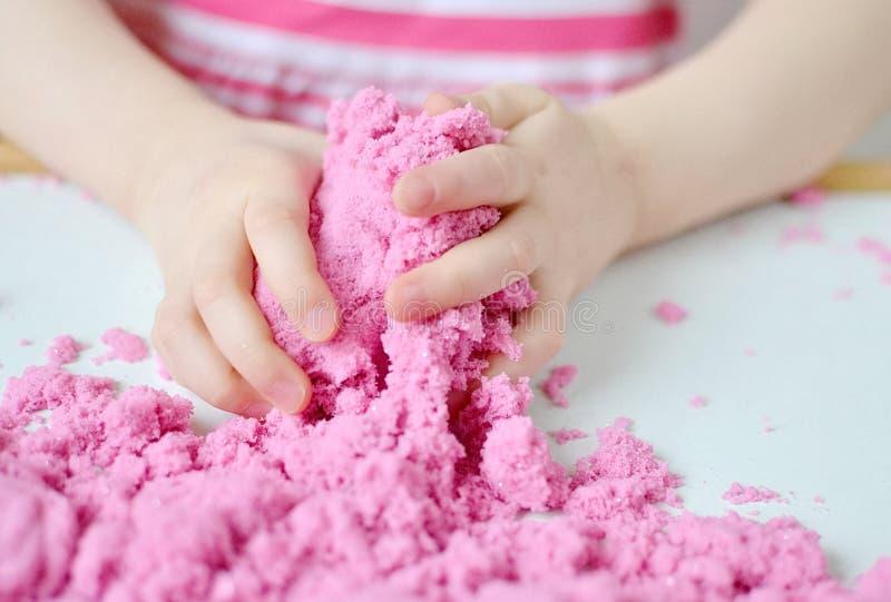 Kleines Mädchen, das zu Hause mit der rosa kinetischen Sand-Früherziehung sich vorbereitet für Schulentwicklungs-Kinderspiel spie lizenzfreie stockbilder