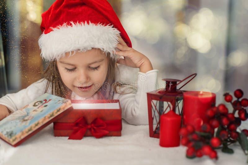 Kleines Mädchen, das zur Zeit Kasten öffnet Magisches glänzendes Geschenk stockbild