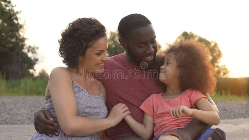 Kleines Mädchen, das zusammen Eltern mit Liebe, harmonische Familie glücklich betrachtet lizenzfreies stockfoto