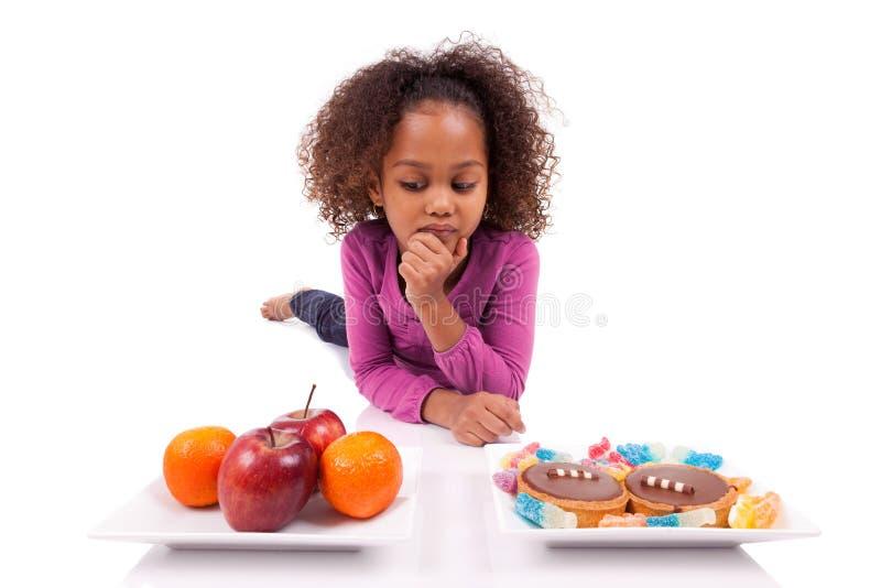 Kleines Mädchen, das zwischen Früchten oder Süßigkeit zögert stockbilder