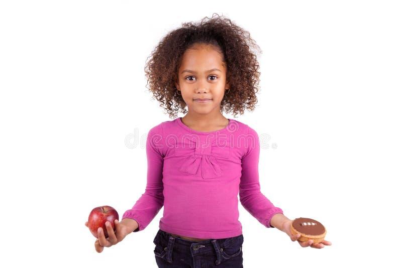 Kleines Mädchen, das zwischen Früchten oder Süßigkeit zögert lizenzfreie stockbilder