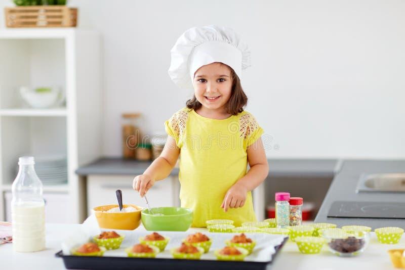 Kleines Mädchen in den Chefs Toque-Backenmuffins zu Hause stockfotografie