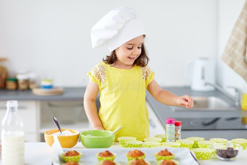 Kleines Mädchen in den Chefs Toque-Backenmuffins zu Hause stockbilder