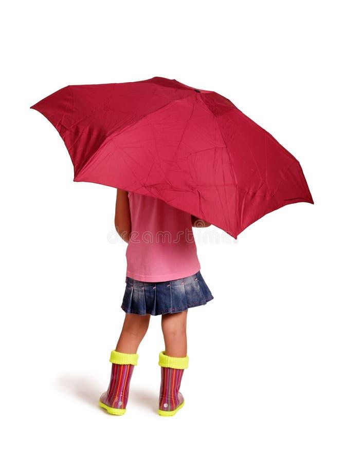 Kleines Mädchen in den Gummistiefeln steht unter einem Regenschirm, auf Weiß stockbild