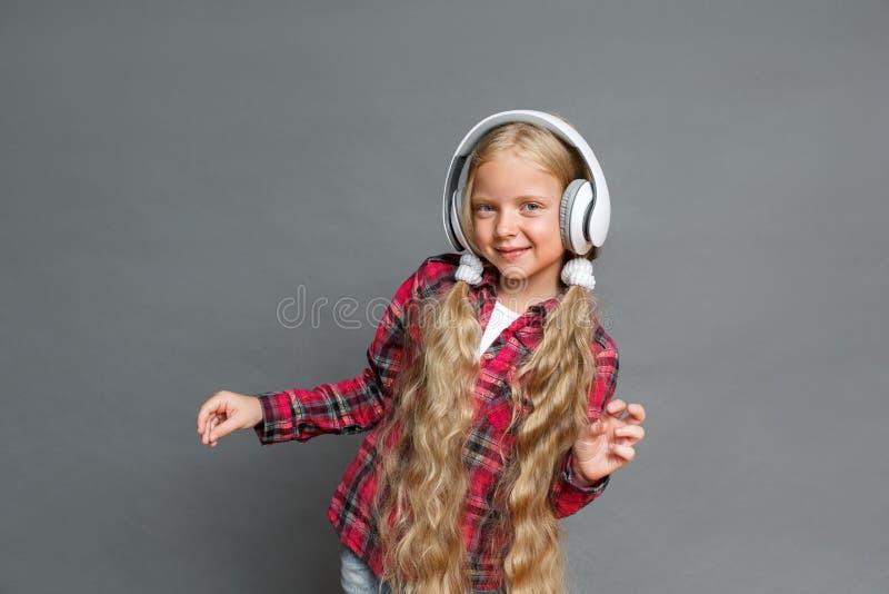 Kleines Mädchen in den Kopfhörern mit den Pferdeschwänzen, die lokalisiert auf dem grauen hörenden Musiktanzen froh stehen lizenzfreies stockfoto