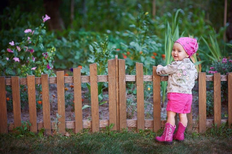 Kleines Mädchen in den rosa Schuhen nahe dem Zaun stockfotografie