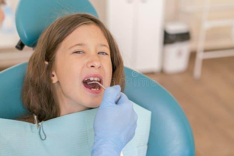Kleines Mädchen an der Aufnahme im dentist& x27; s-Büro Kleines Mädchen, das in einem Stuhl nahe einem Zahnarzt nach zahnmedizini lizenzfreie stockfotos