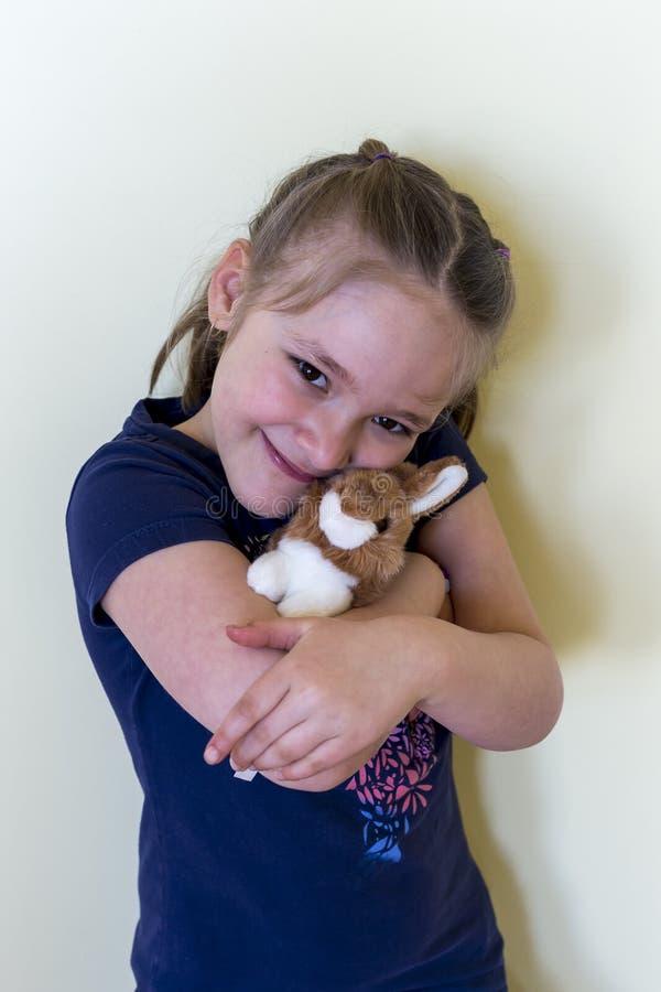 Kleines Mädchen in der dunkelblauen Spitzenholding füllte Spielzeugkaninchen an lizenzfreie stockfotos