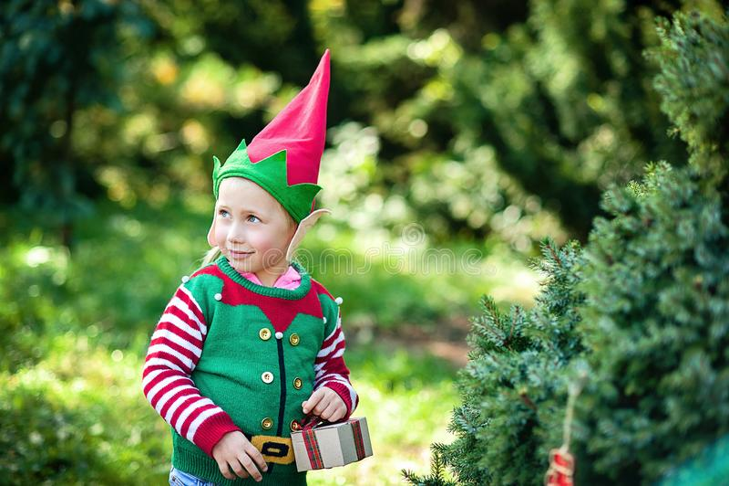 Kleines Mädchen in der Elfenstrickjacke und -hut, die auf ein Weihnachten im Holz warten Brustbild eines kleinen Kindes nahe dem  stockbild