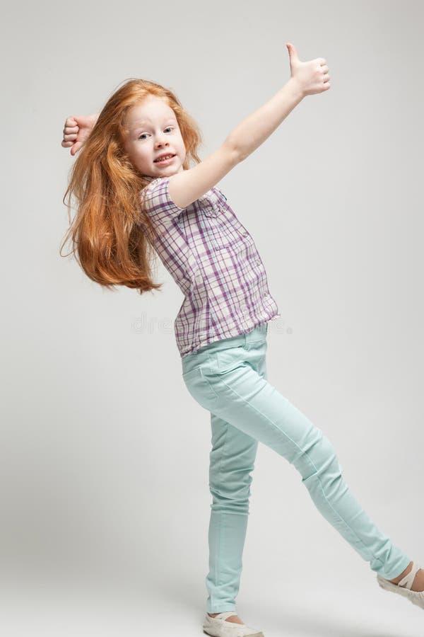 Kleines Mädchen der entzückenden netten Rothaarigen im karierten Hemd, in der hellen blauen Hose und in den weißen Stiefeln stockbild