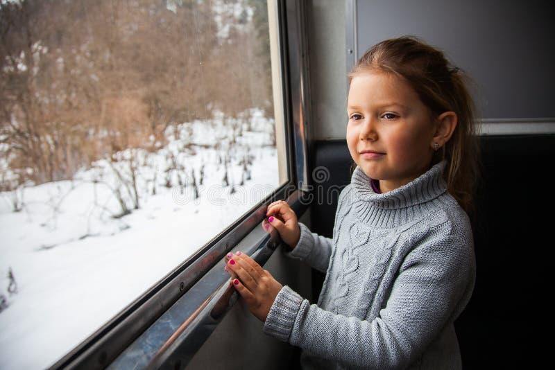 Kleines Mädchen in der grauen Strickjacke, die mit dem Kukushka-Zug in Georgia reist und während des Fensters schaut lizenzfreie stockfotos