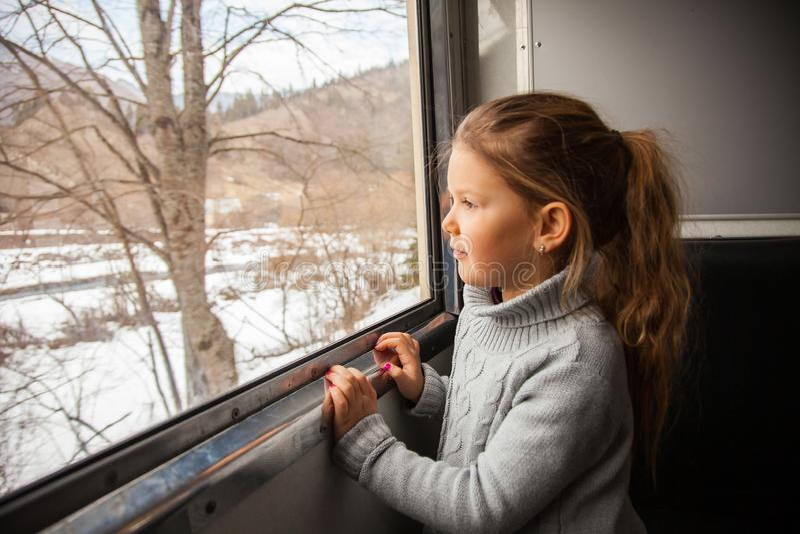 Kleines Mädchen in der grauen Strickjacke, die mit dem Kukushka-Zug in Georgia reist und während des Fensters schaut stockbild