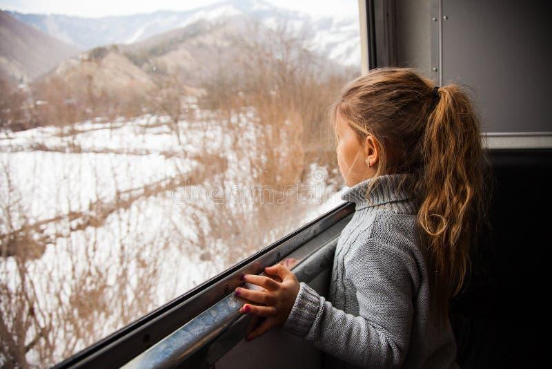 Kleines Mädchen in der grauen Strickjacke, die mit dem Kukushka-Zug in Georgia reist und während des Fensters schaut lizenzfreie stockbilder