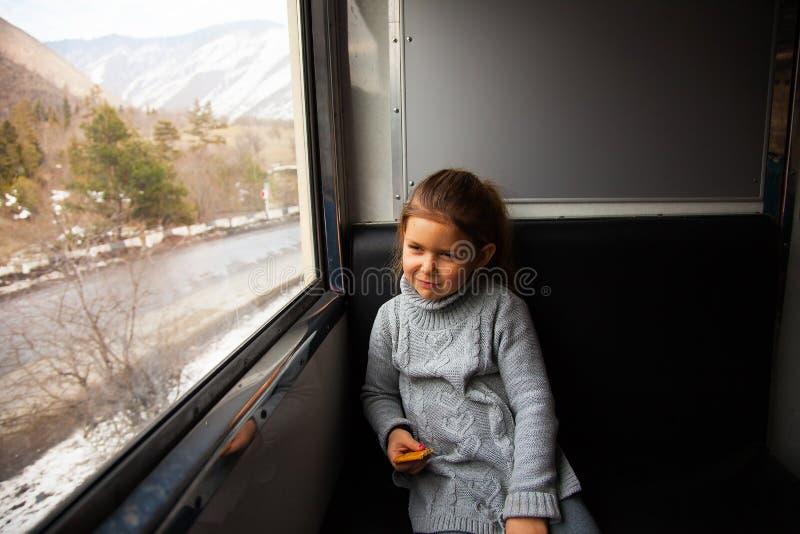 Kleines Mädchen in der grauen Strickjacke, die mit dem Kukushka-Zug in Georgia reist und während des Fensters schaut stockfotografie