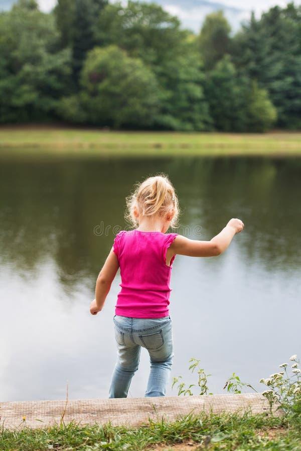 Kleines Mädchen in der Natur durch den See stockbilder