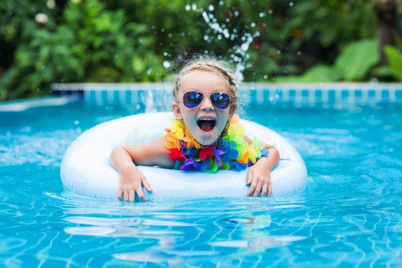 Kleines Mädchen in der Sonnenbrille, die auf den Kreis im Pool an einem Erholungsort in den Tropen schwimmt lizenzfreies stockbild