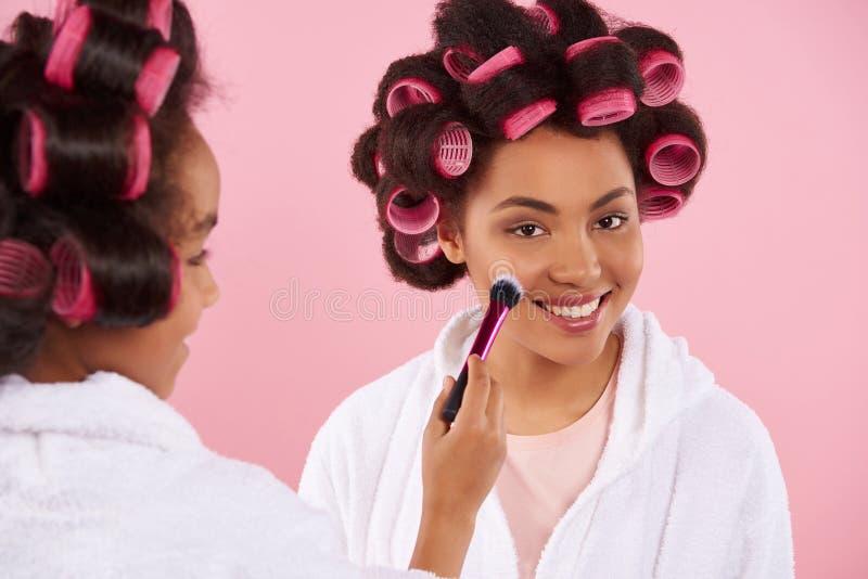 Kleines Mädchen des Afroamerikaners, das Make-up mit Mutter tut stockfoto