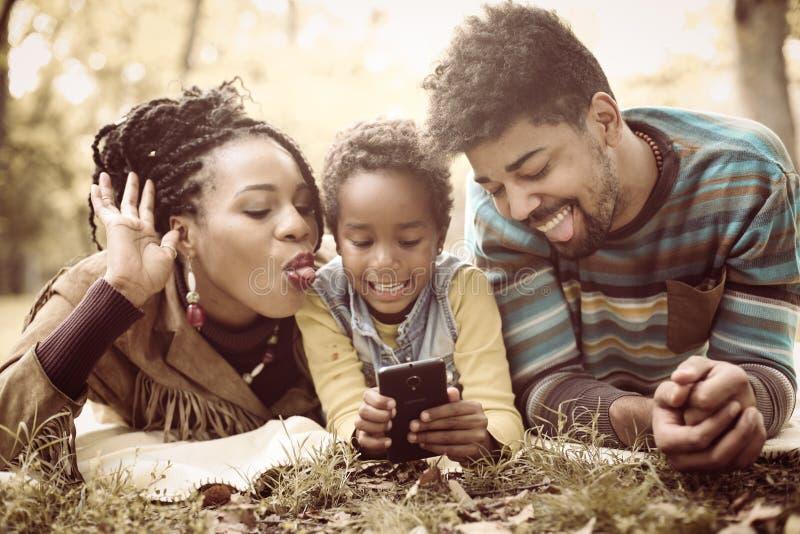 Kleines Mädchen des Afroamerikaners, das Selbstphoto im Park macht stockbild