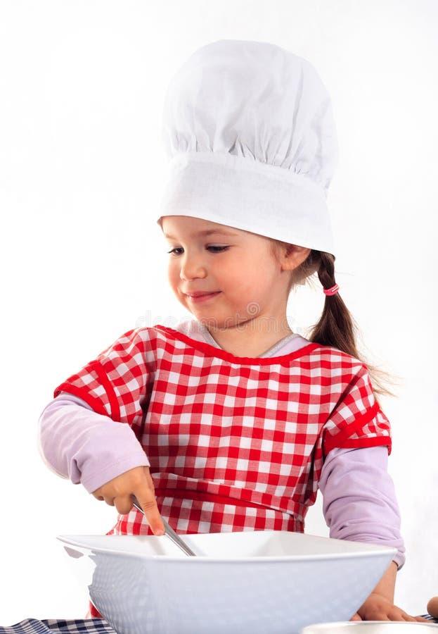 Kleines Mädchen des Lächelns im Kochkostüm stockfotos