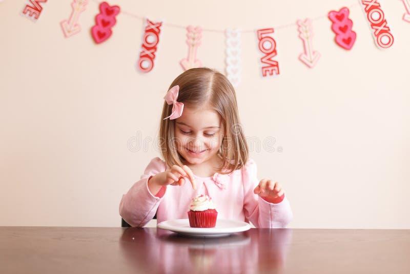 Kleines Mädchen des netten Valentinstags mit kleinem Kuchen lizenzfreies stockfoto