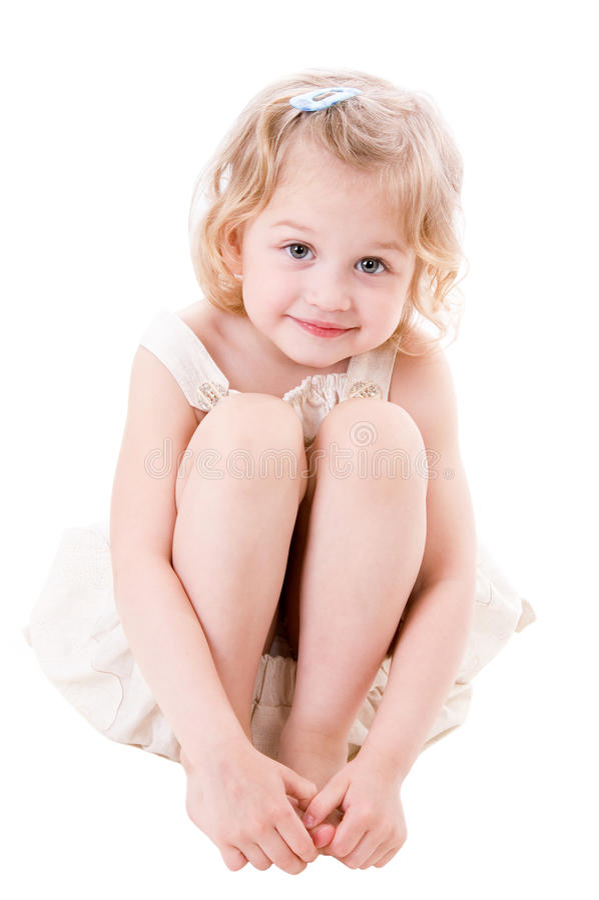 Kleines Mädchen des smiley, das auf Weiß sitzt stockbilder