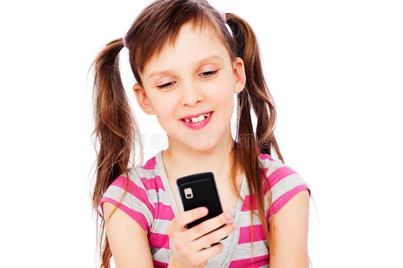 Kleines Mädchen des smiley mit Mobiltelefon stockbilder