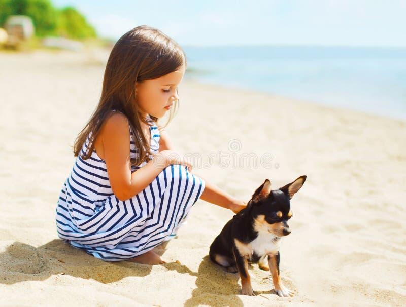 Kleines Mädchen des Sommerporträts mit dem Hund, der zusammen sitzt stockbild