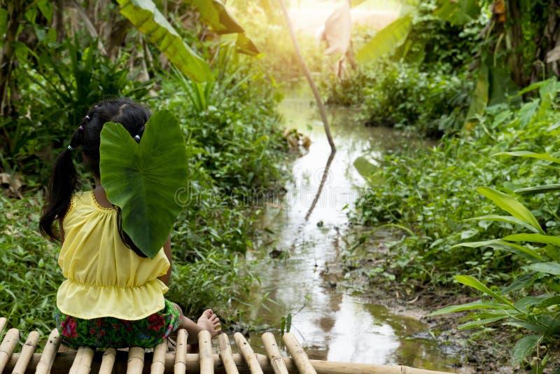 Kleines Mädchen des Thailänders, das durch den Fluss sitzt stockfotos