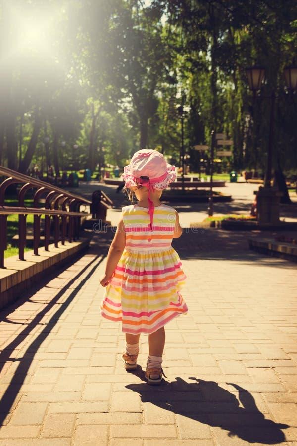 Kleines Mädchen des Weinleseporträts im schönen Kleid, das weg in den Park läuft lizenzfreie stockfotografie