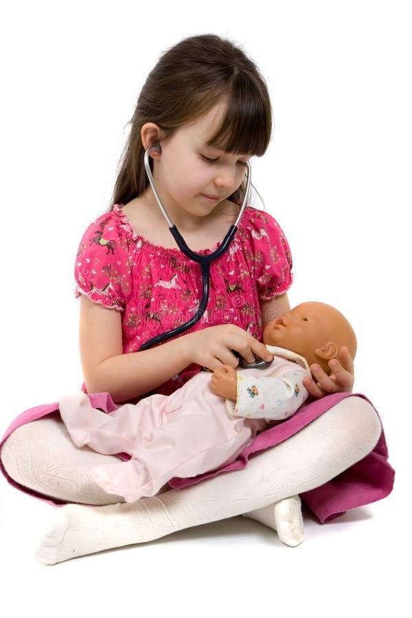 Kleines Mädchen-Doktor With Stethoscope und Puppe stockfoto