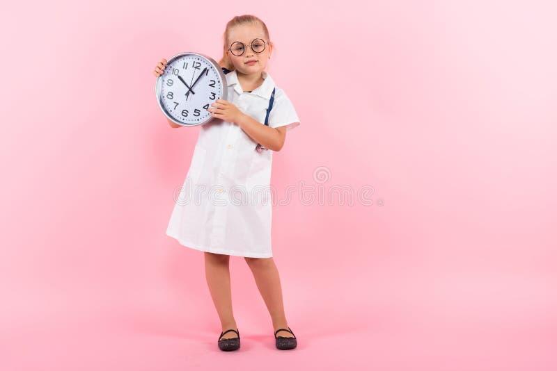 Kleines Mädchen in Doktorkostüm mit Uhren stockbilder