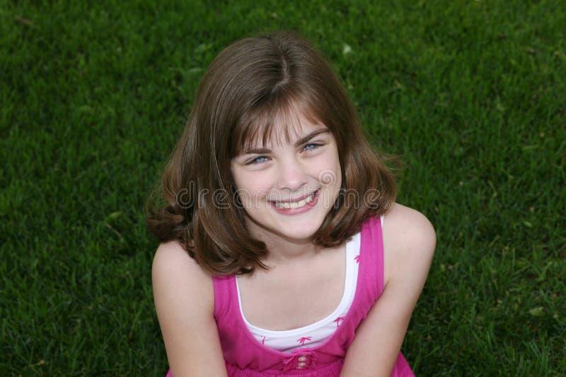 Kleines Mädchen draußen im Gras stockfotografie